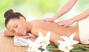 Woman getting a massage surrounded by white flowers.