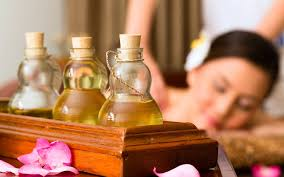 Bottles of oil with woman getting massage.