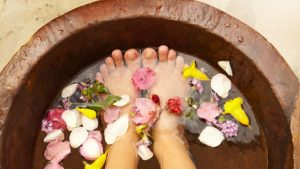Woman soaking feet in tub of water and petals.