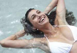 Woman smiling while floating on her back in water.