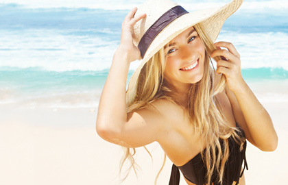 Blonde-haired woman on beach wearing a hat.