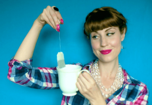Woman holding tea bag over tea cup.
