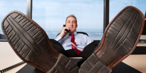Man talks on phone with his feet up on desk.