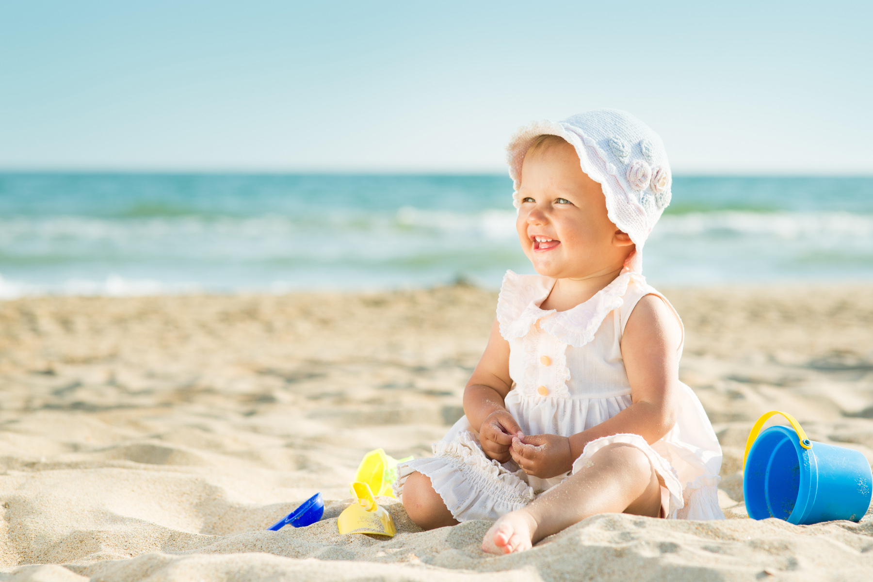 Smiling baby girl on the beach.