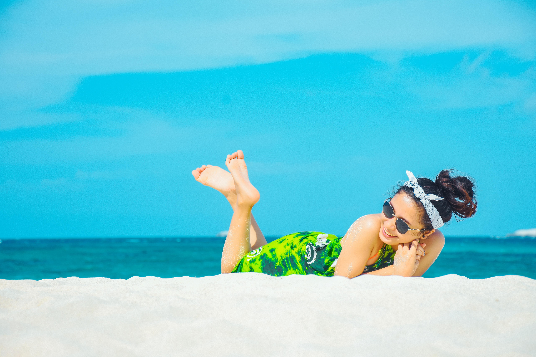 Woman laughing on beach wearing sunglasses.