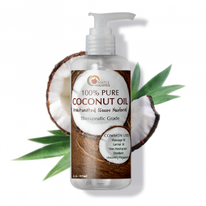Bottle of coconut oil with pump, with coconut in background.