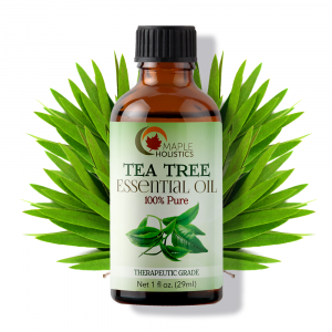Bottle of tea tree essential oil with greenery in background.