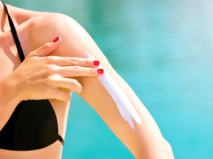 Woman applying sunscreen to her arm.
