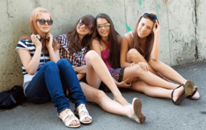Teenage girls sitting together against a wall.