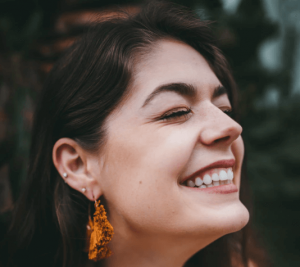 Woman smiling with butterfly earring.