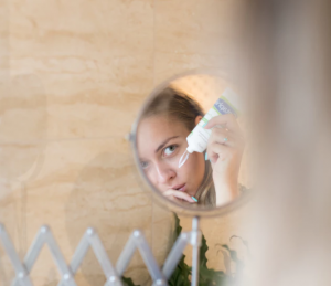 Woman applying cream in a mirror.