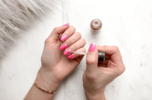 Applying pink nail polish.