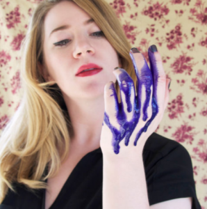 Blonde-haired woman looking at hand filled with purple shampoo.
