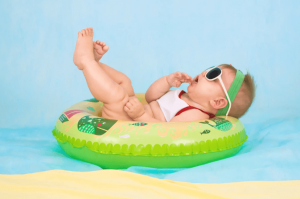 Baby lounging in inflatable in water.