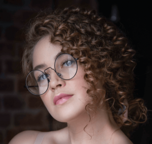 Woman with curly hair wearing glasses.