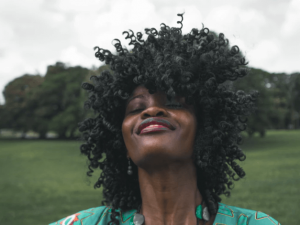 Woman with curly hair smiling.