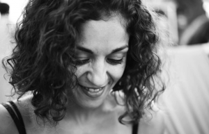 Smiling woman with short, curly hair.