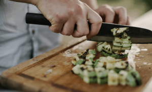 Woman using knife to cut up zucchini.