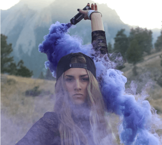 Blonde-haired woman in field with purple smoke.