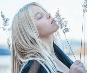 Blonde-haired woman smelling flower.
