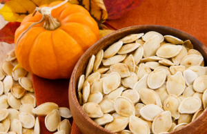 Bowl of pumpkin seeds next to pumpkin.