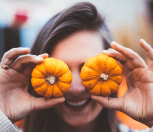 Woman covering her eyes with pumpkins.