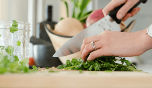 Woman with ring chopping herbs.