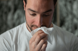Man wiping nose with tissue.