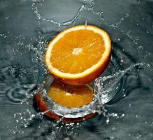 Sliced orange falling into water