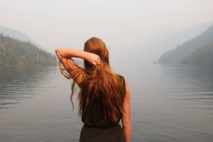 Girl with long red hair at a lake