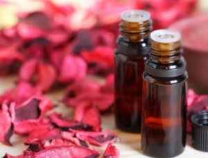 Petals and two vials of rosewood essential oil.