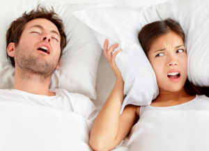 Man snoring and woman covering her ears with a pillow.