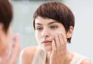 Woman applying cream to face.