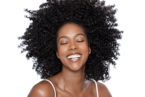 Woman smiling with curly black hair.