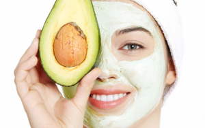 Woman wearing face mask covering one eye with half an avocado.