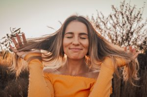 Woman smiling while holding up her hair