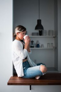 Woman sitting and drinking from mug.