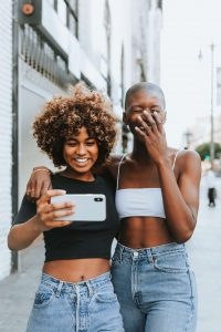 Two women laughing while taking a selfie.