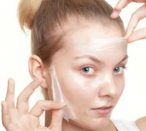 Woman peeling her face.