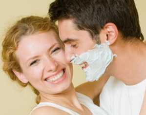 Man with shaving cream smiling at smiling woman.
