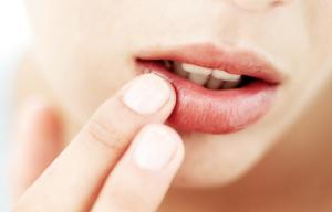 Woman applying lip scrub.
