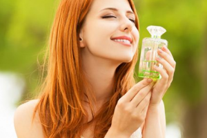 Woman smelling green perfume.