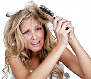 Woman struggling to brush her hair.