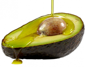 Half an avocado with oil being poured on it.