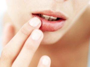 Woman applying product to her lips.