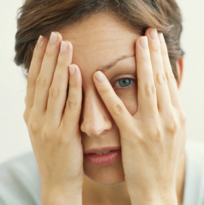 Woman covering her eyes and peaking through fingers.