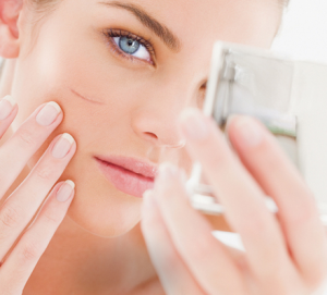 Woman looking at scar on cheek in compact mirror.