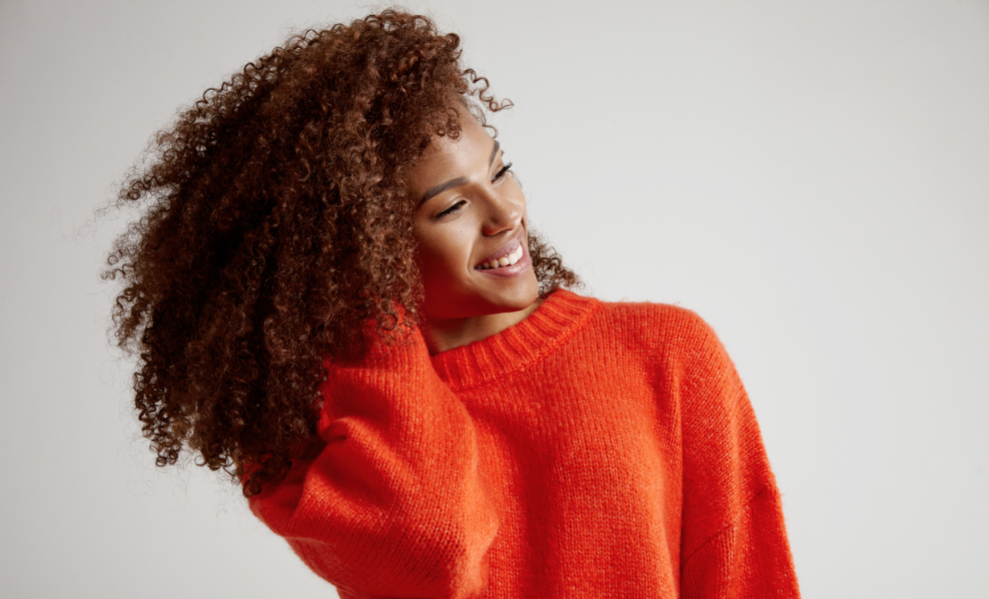 Woman with curly hair and orange sweater.