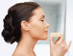 Women Smelling A Bar Of Soap.