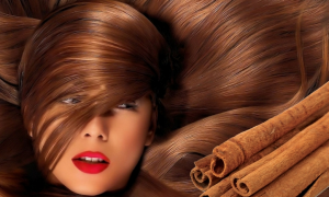 Woman's face covered by her hair next to cinnamon sticks.